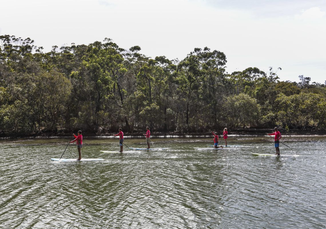 Group enjoying a stand-up paddleboarding tour with Wajaana Yaam Gumbaynggirr Adventure Tours at Moonee Creek, Coffs Harbour, North Coast