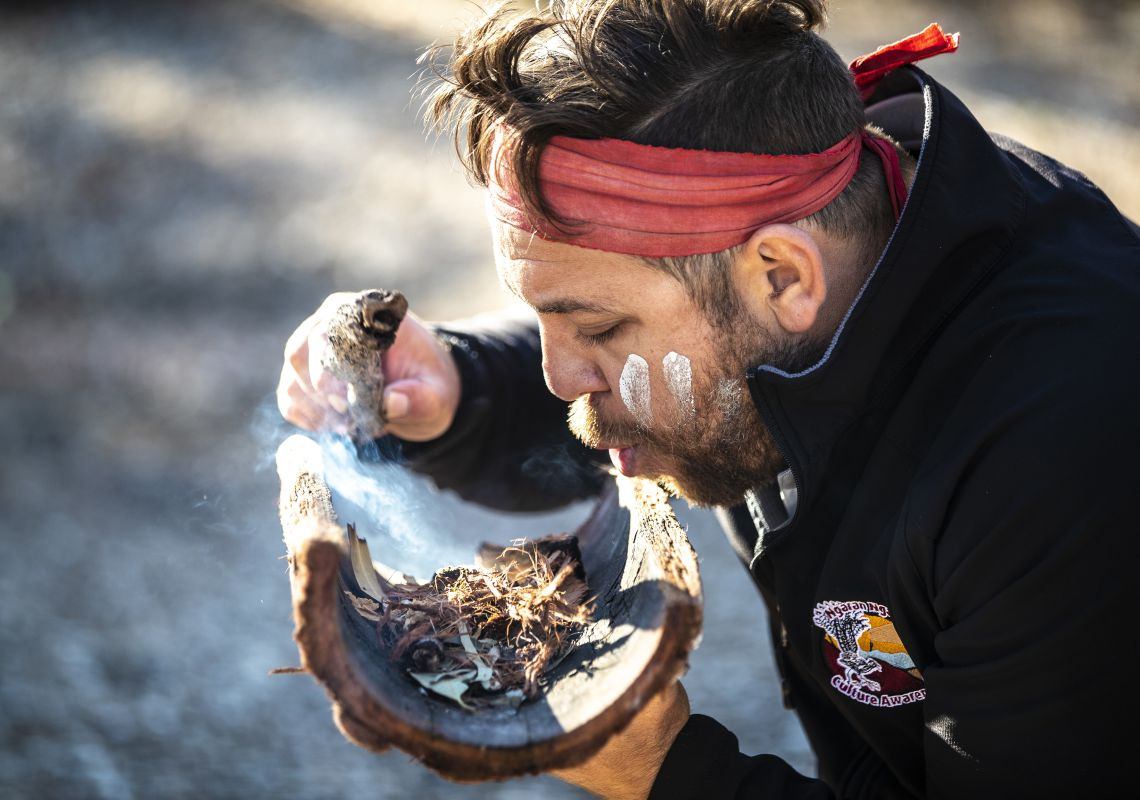Aboriginal guide Dwayne Bannon-Harrison performing a smoking ceremony during a traditional welcome on a Ngaran Ngaran Culture Awareness tour