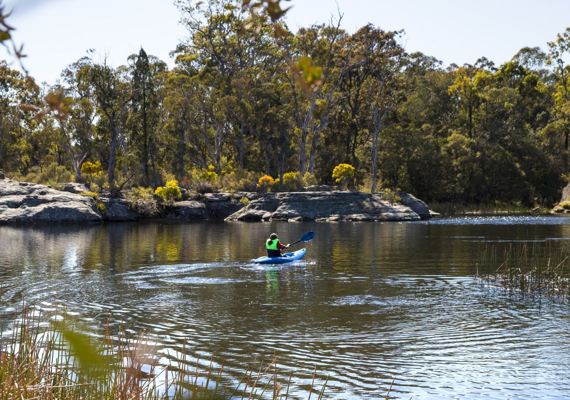 Woman enjoying an afternoon kayak through Dunns Swamp in Wollemi National Park