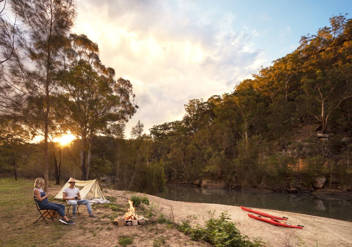 Couple enjoying a campfire by their tent on the Hawkesbury River in Lower MacDonald