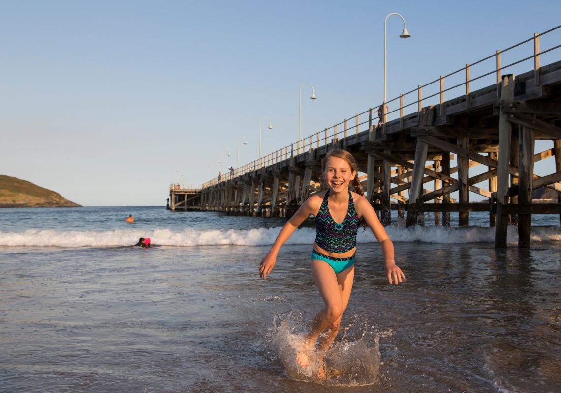 A young girl enjoying the beach at the Coffs Harbour jetty in Coffs Coast, North Coast