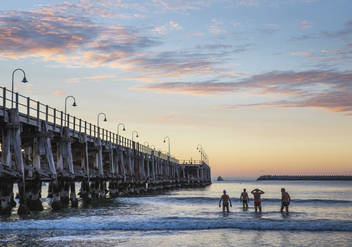 Men enjoying a morning swim as the sun rises over the pier at Jetty Beach in Coffs Harbour, North Coast