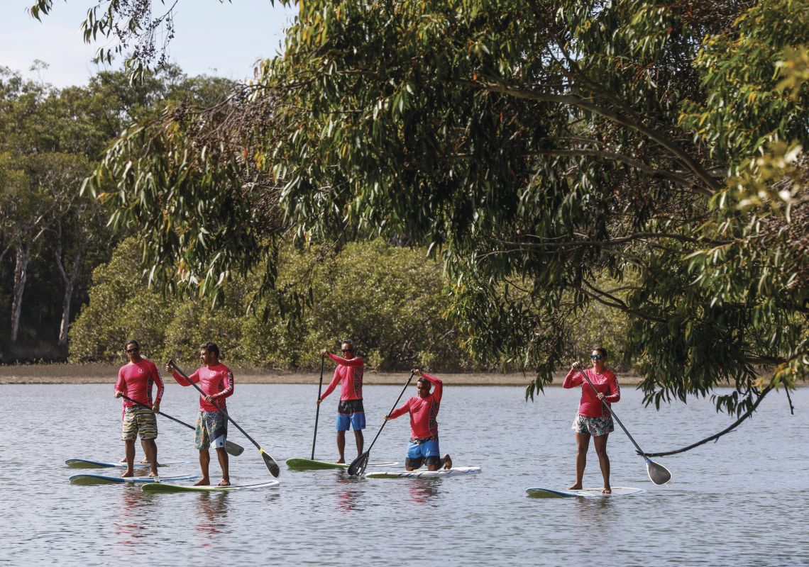 Group enjoying a stand-up paddleboarding tour with Wajaana Yaam Gumbaynggirr Adventure Tours at Moonee Creek on the Coffs Coast, North Coast