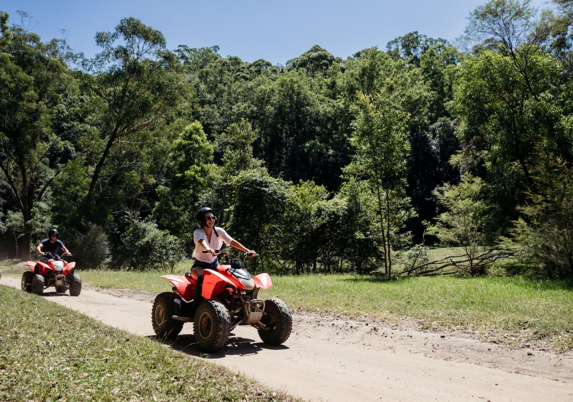 Friends enjoying a guided tour on quad bikes at Glenworth Valley in the Central Coast.