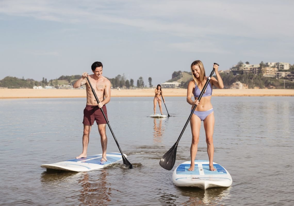 Couple enjoying a day of stand up paddleboarding on Terrigal Lagoon in Terrigal, Central Coast