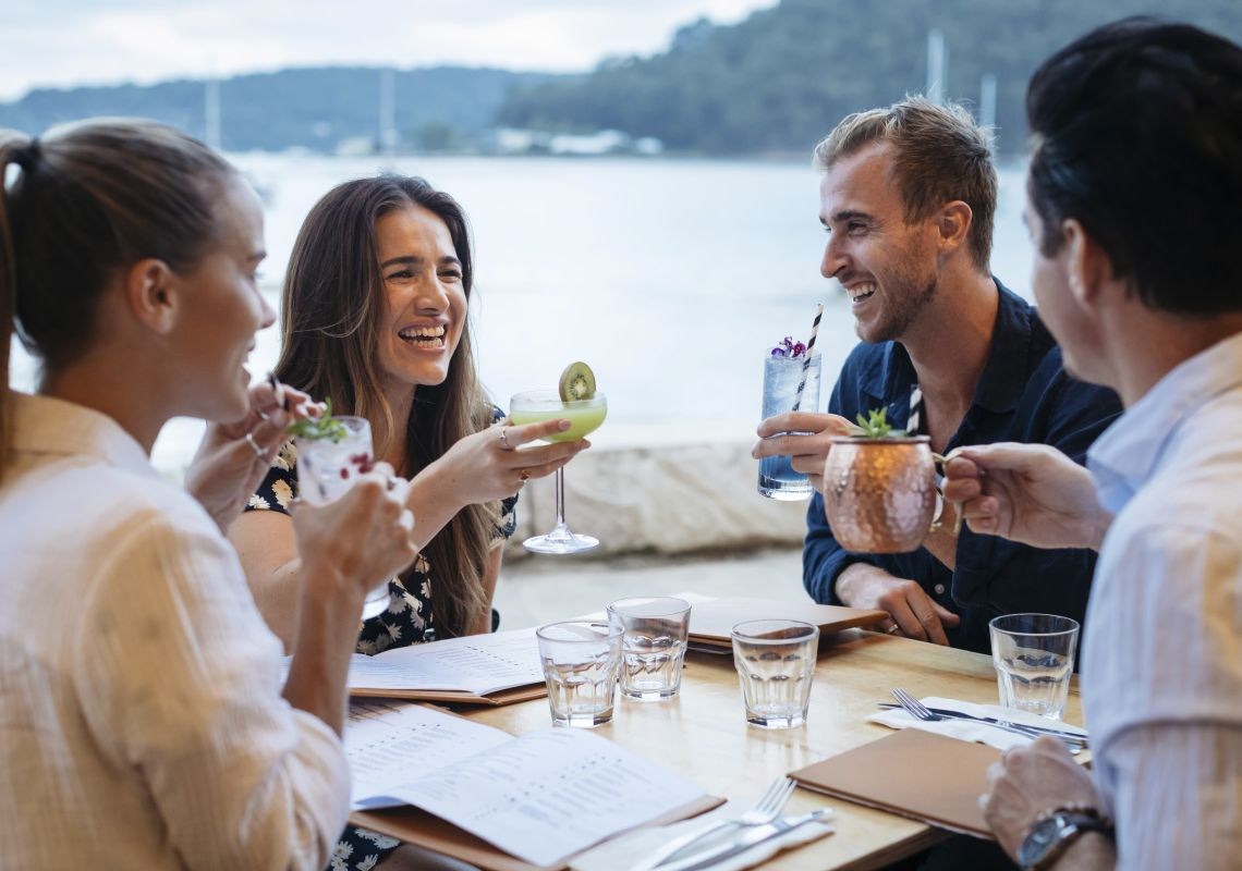 Friends enjoying evening drinks at The BOX on the Water restaurant and bar at Ettalong Beach, Central Coast