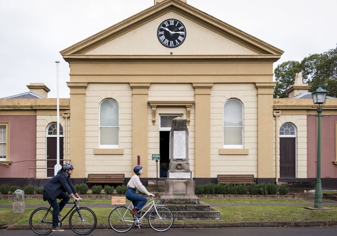 Couple riding past the Morpeth Museum in Morpeth, Hunter Valley