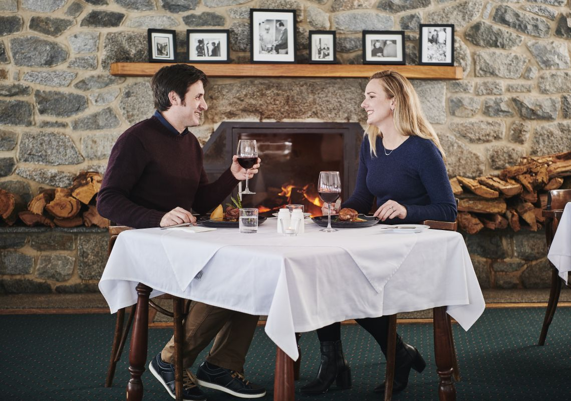 Couple enjoying a meal by the fireplace at Marritz Hotel in Perisher, Snowy Mountains