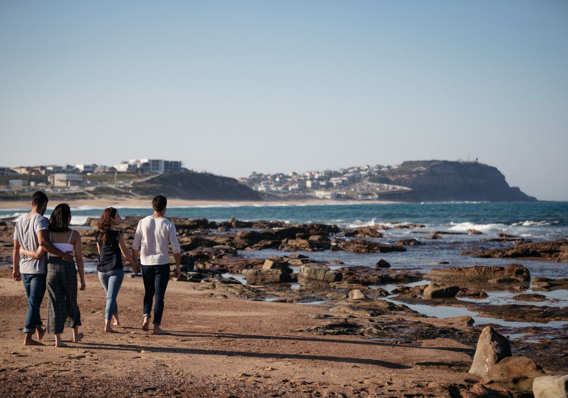 People enjoying a walk along Merewether Beach in Newcastle