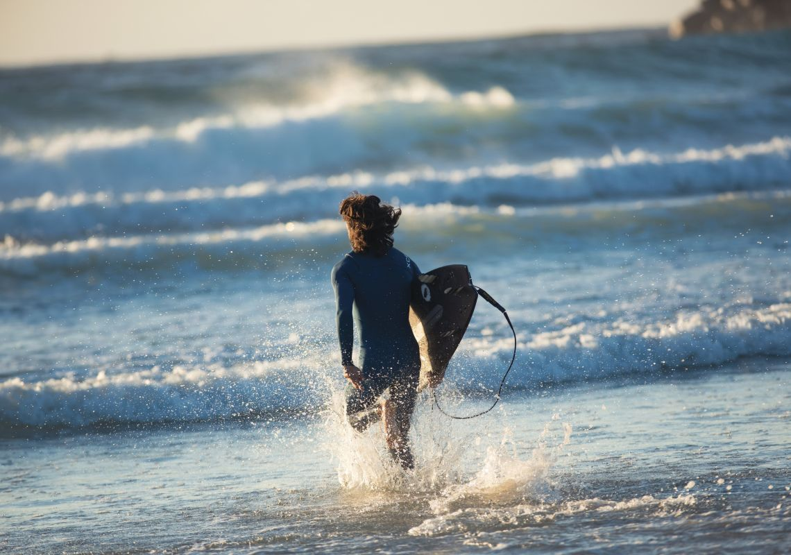 Surfer heading out for a morning surf at Duranbah Beach in Tweed Heads