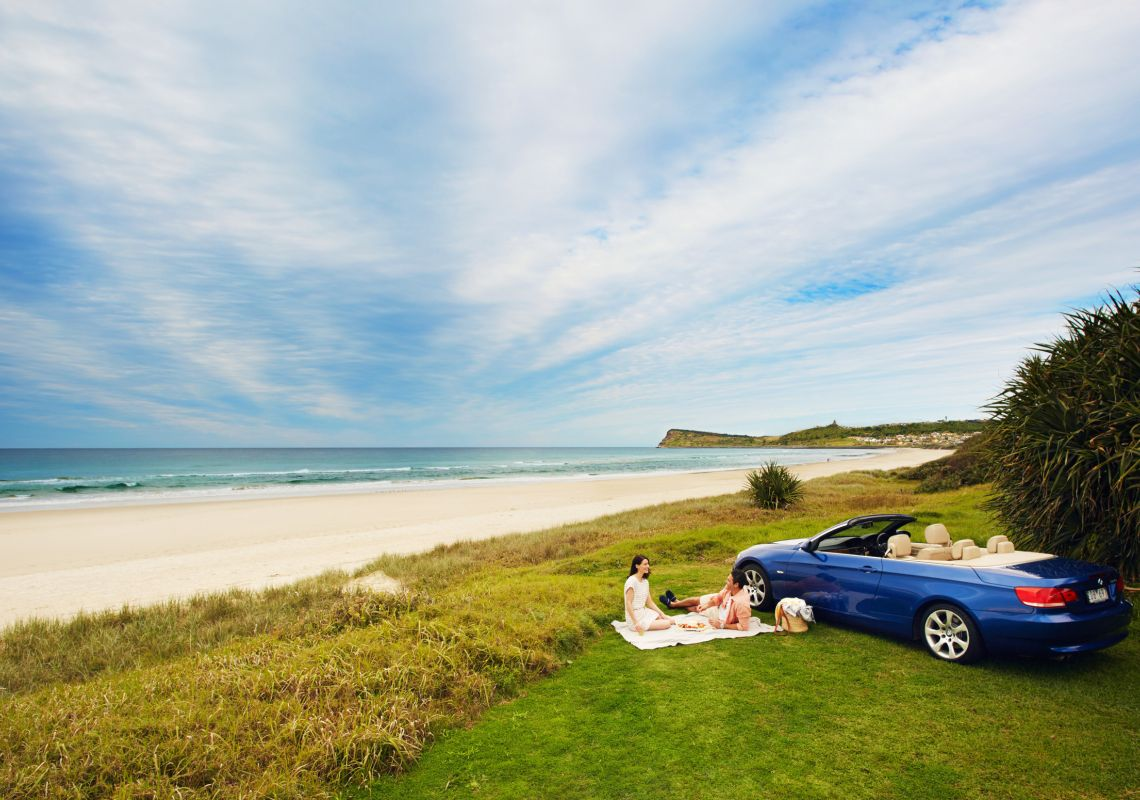 Couple enjoying a picnic overlooking Lennox Head Beach in Lennox Head, Byron Bay