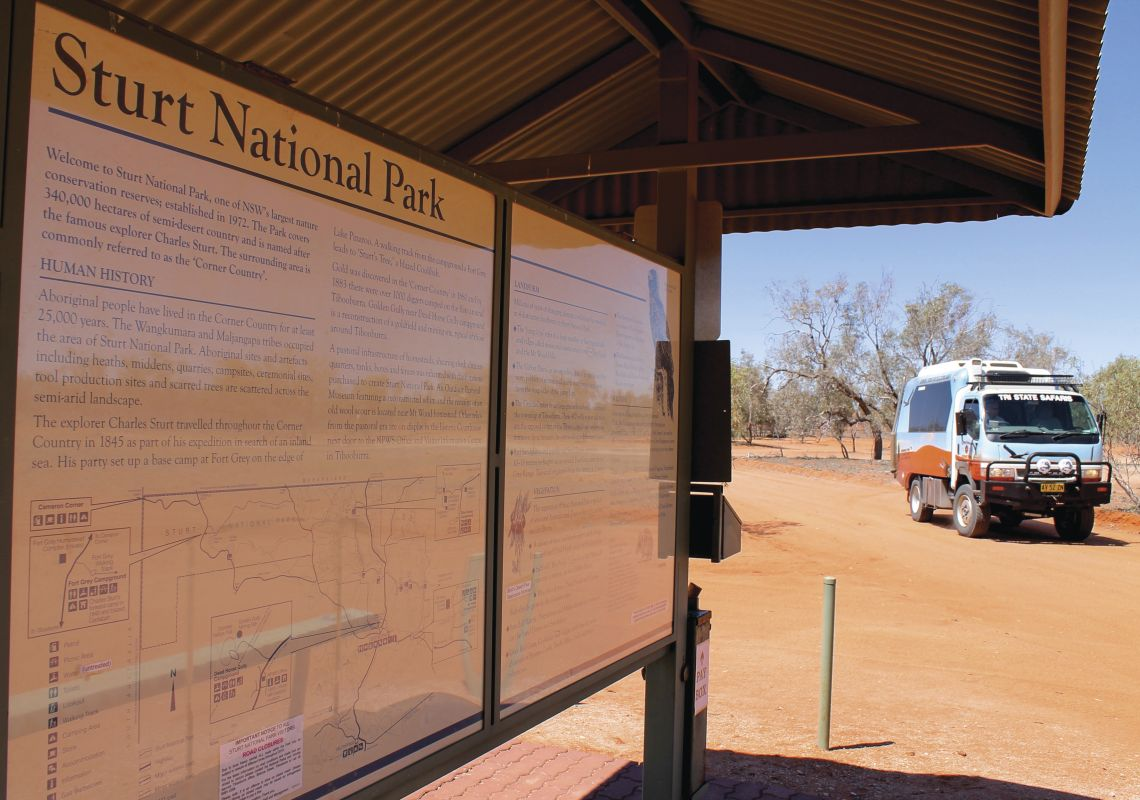 Tri State Safari's bus parked by an information sign in Sturt National Park