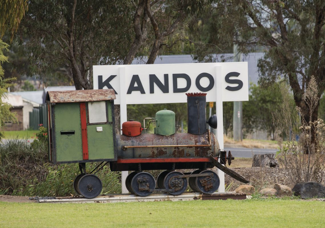 Mini steam train sits alongside a Kandos train station sign in Kandos , Mudgee