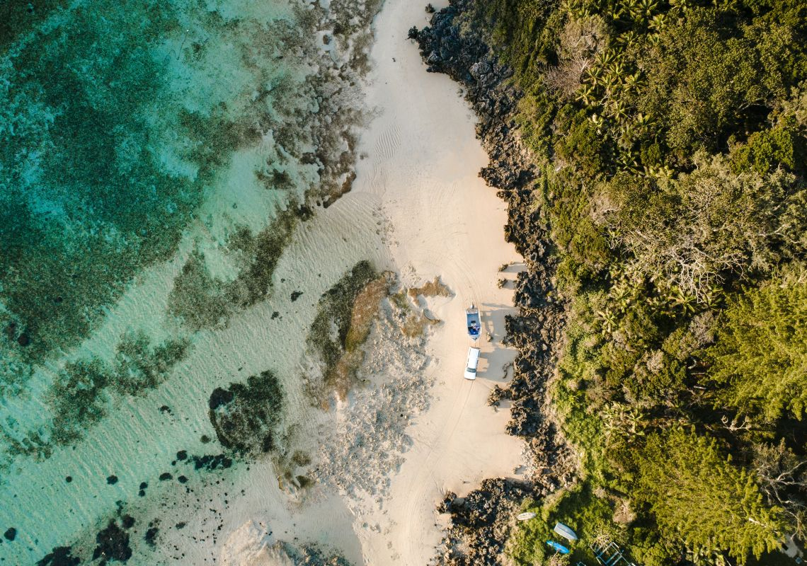 Aerial overlooking a car and boat trailer on The Lagoon Beach, Lord Howe Island