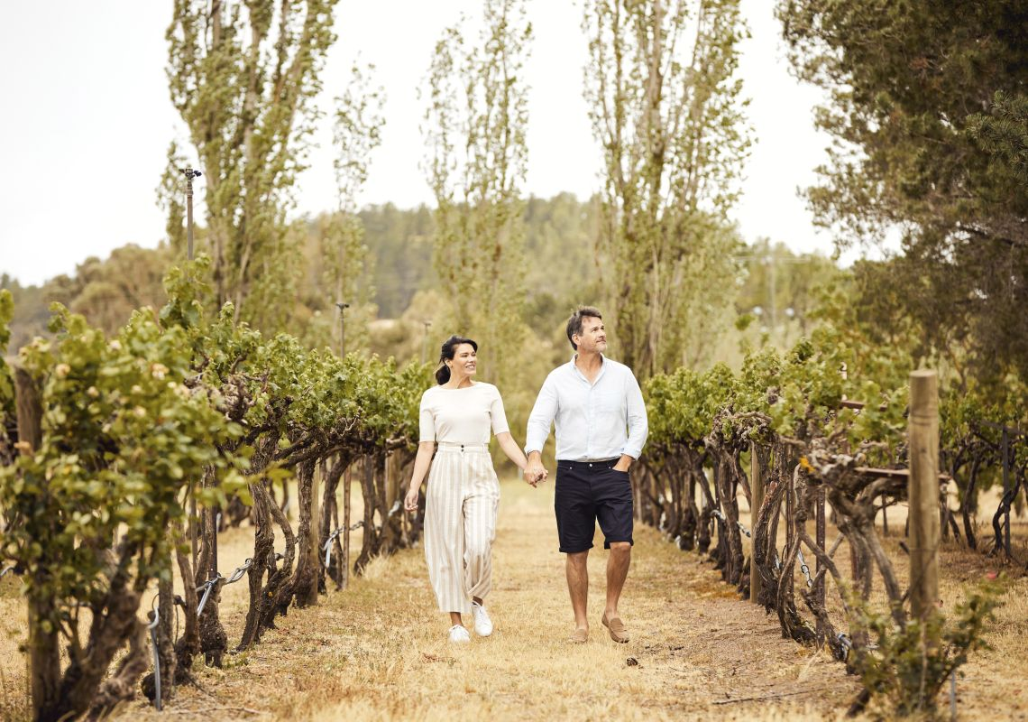 Couple enjoying a walk through the Helm Wines vineyard in Murrumbateman, Yass Area