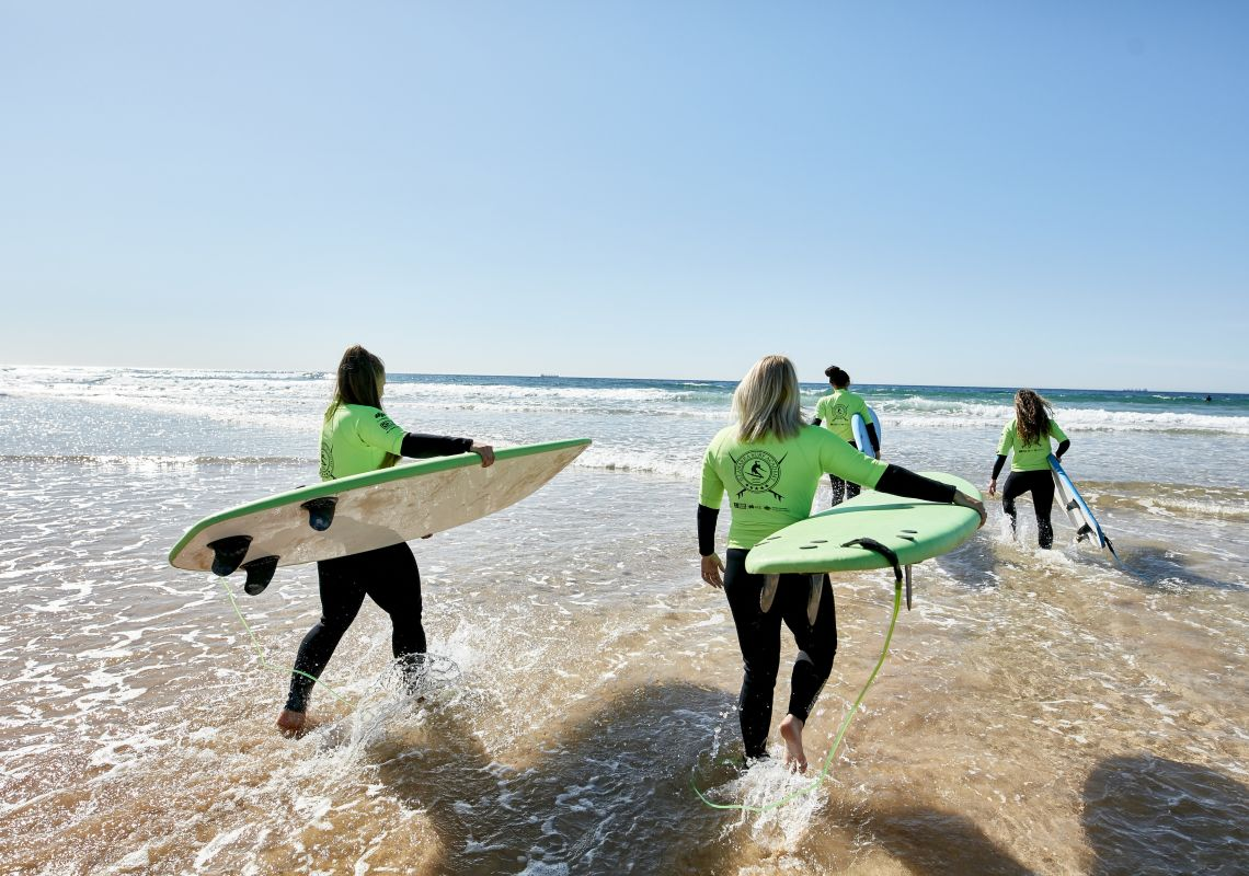 Women learning how to surf with Illawarra Surf Academy on Corrimal Beach near Wollongong, South Coast