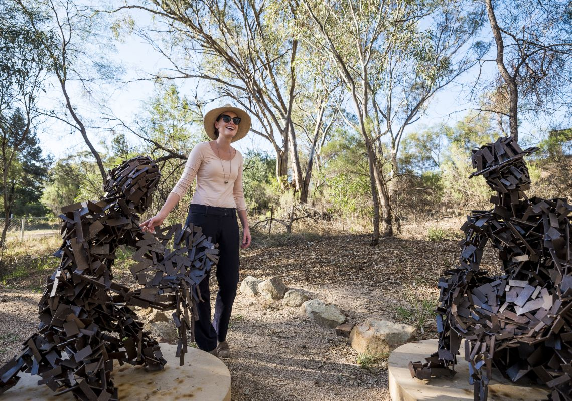 Woman enjoying the sculptures on a visit to the Peak Hill Open Cut Gold Mine in Peak Hill, Parkes Area