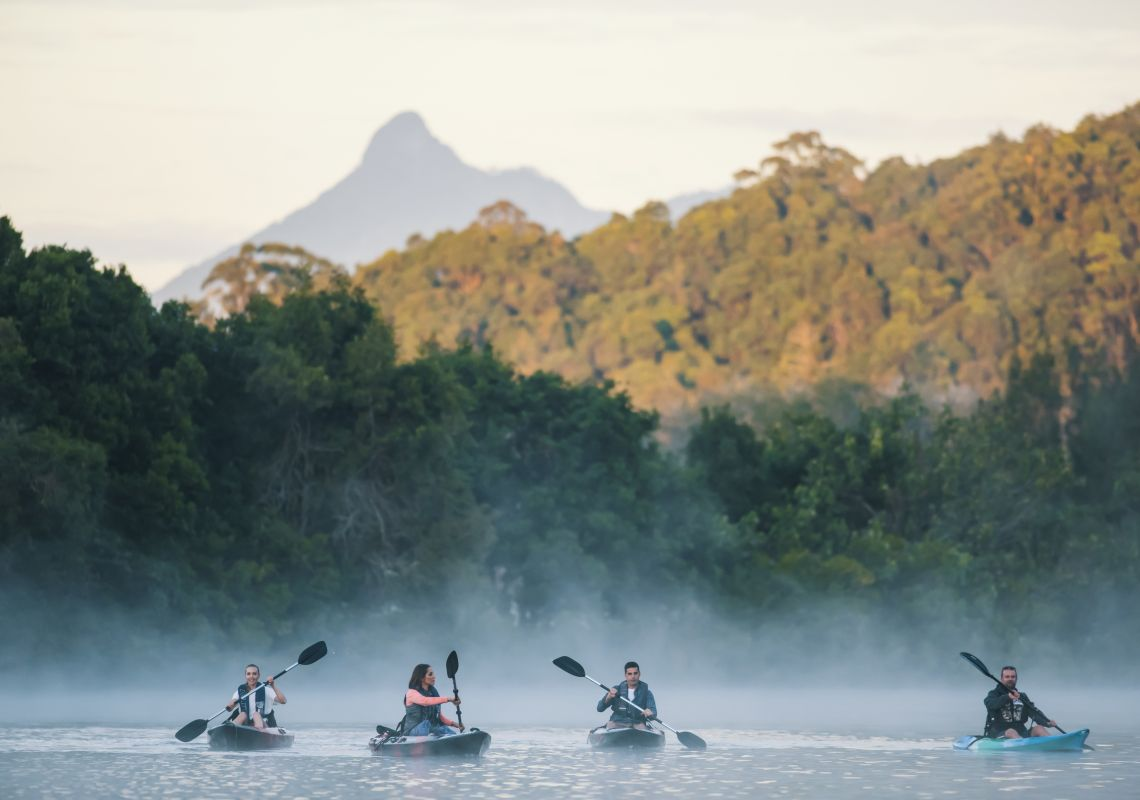 Friends enjoying an early morning kayak tour on Tweed River with scenic views of Mount Warning, North Coast