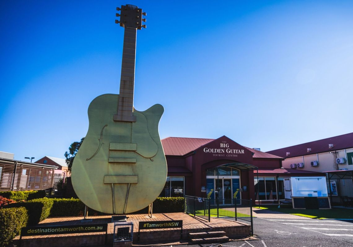 Big Golden Guitar statue in front of Visitor information centre building on a clear blue sky day