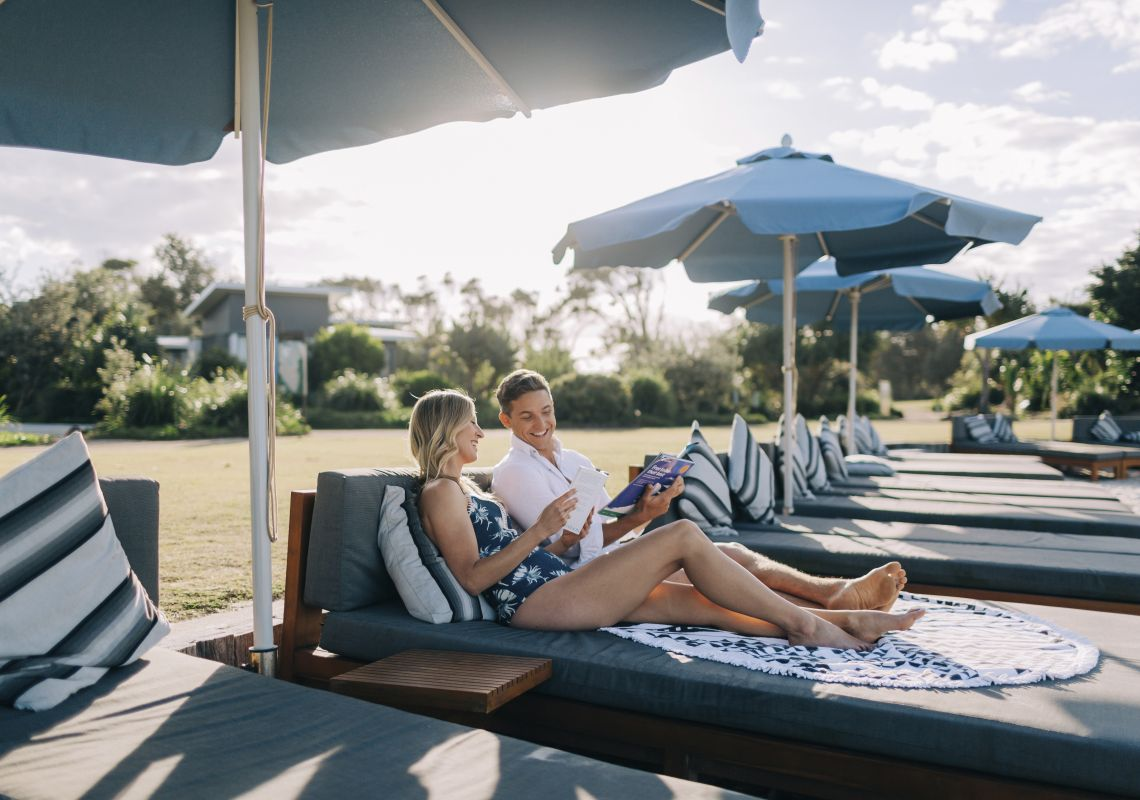 Couple relaxing at the Botanica Beach Club, exclusive to guests staying at Elements of Byron Resort, Byron Bay
