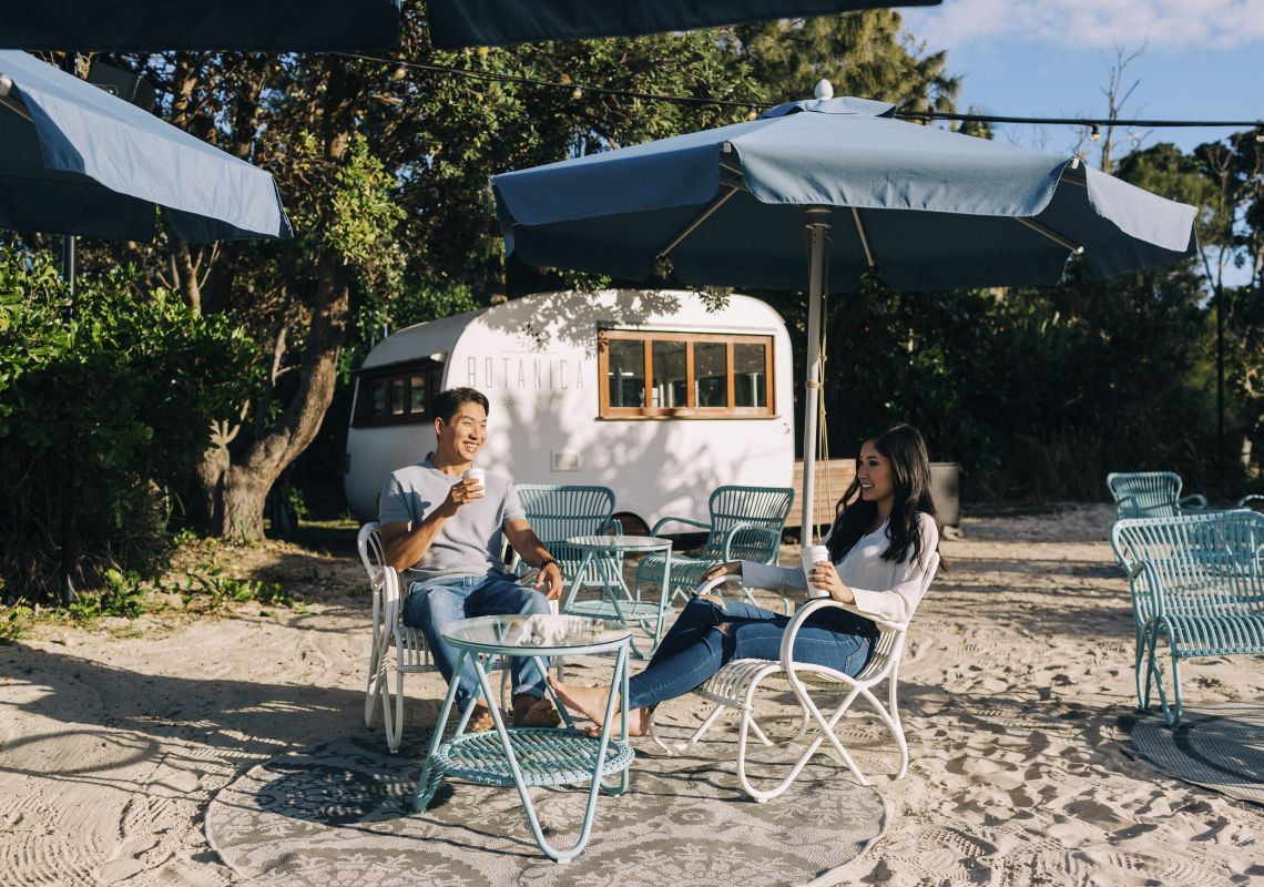 Couple relaxing at the Botanica Beach Club, exclusive to guests staying at Elements of Byron Resort, Byron Bay, North Coast