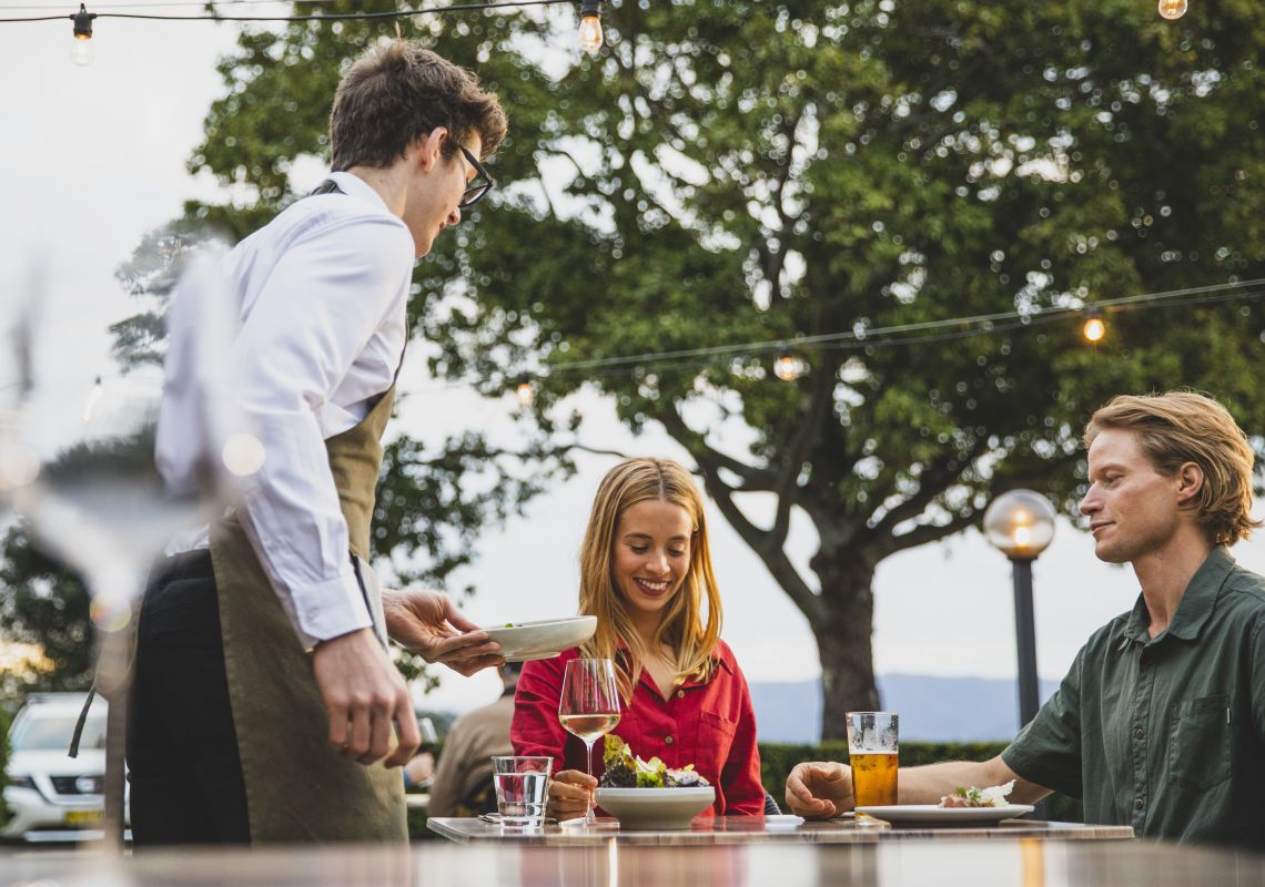 Couple enjoying food and drink at Bellingen Valley Lodge's onsite restaurant, Hilltop at the Lodge