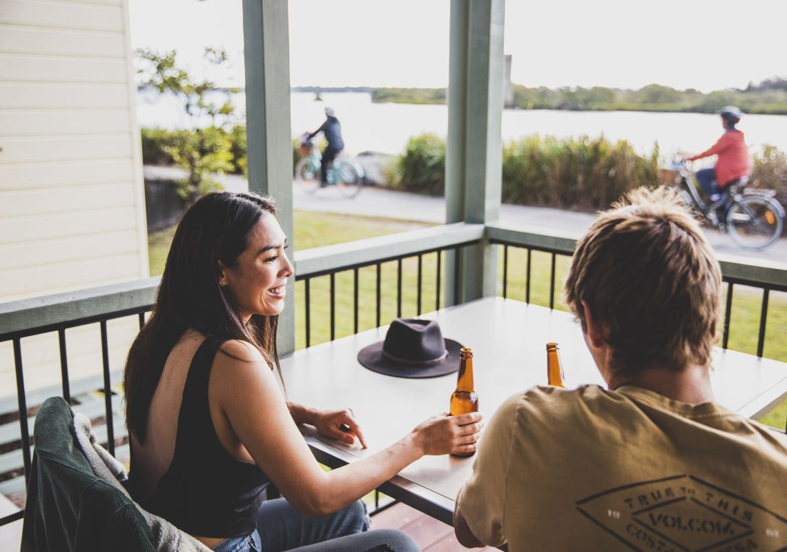 Couple enjoying scenic views from their waterfront villa at Calypso Yamba Holiday Park in Yamba, Clarence Valley