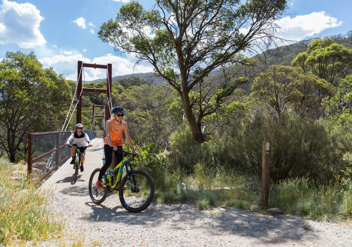 Mountain bikers travelling over a footbridge on the Thredbo Valley Track, Kosciuszko National Park
