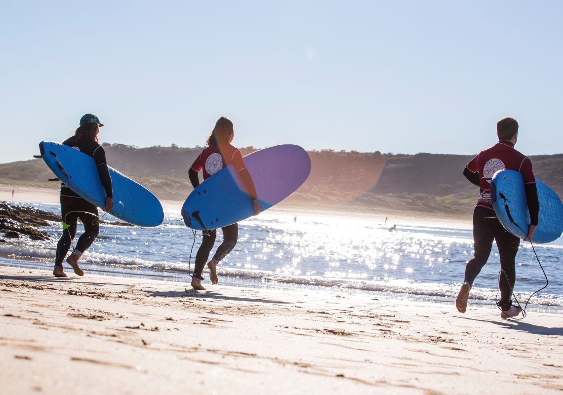 Couple learning to surf with Pines Surfing Academy Surf School at Killalea Beach ('The Farm'), Shell Cove, Shellharbour