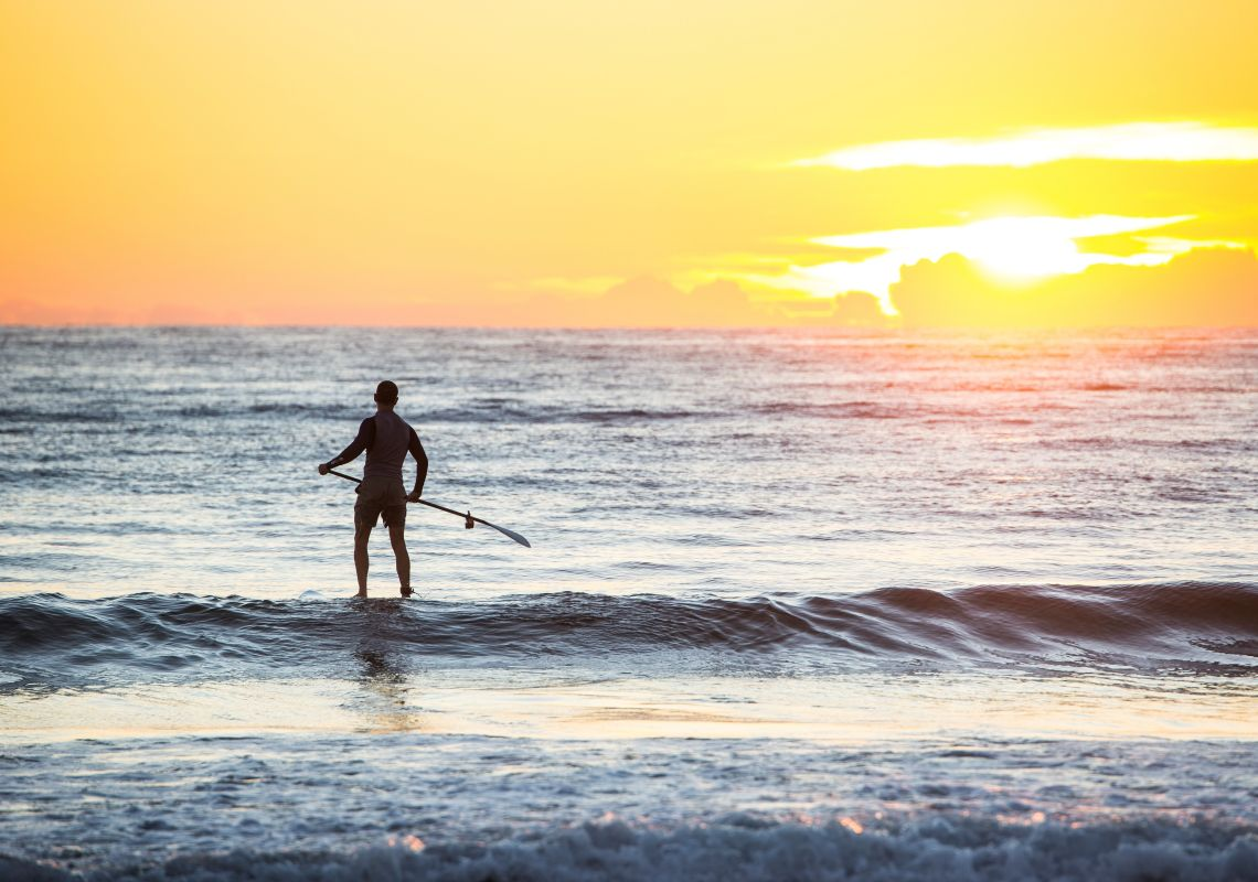Man heading out for a morning of stand-up paddleboarding at Tathra Beach in Tathra, Sapphire Coast