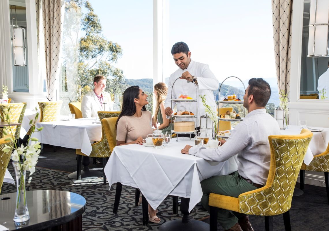 Couple enjoying a premium afternoon high tea at the Wintergarden restaurant within The Hyrdo Majestic Hotel, Medlow Bath