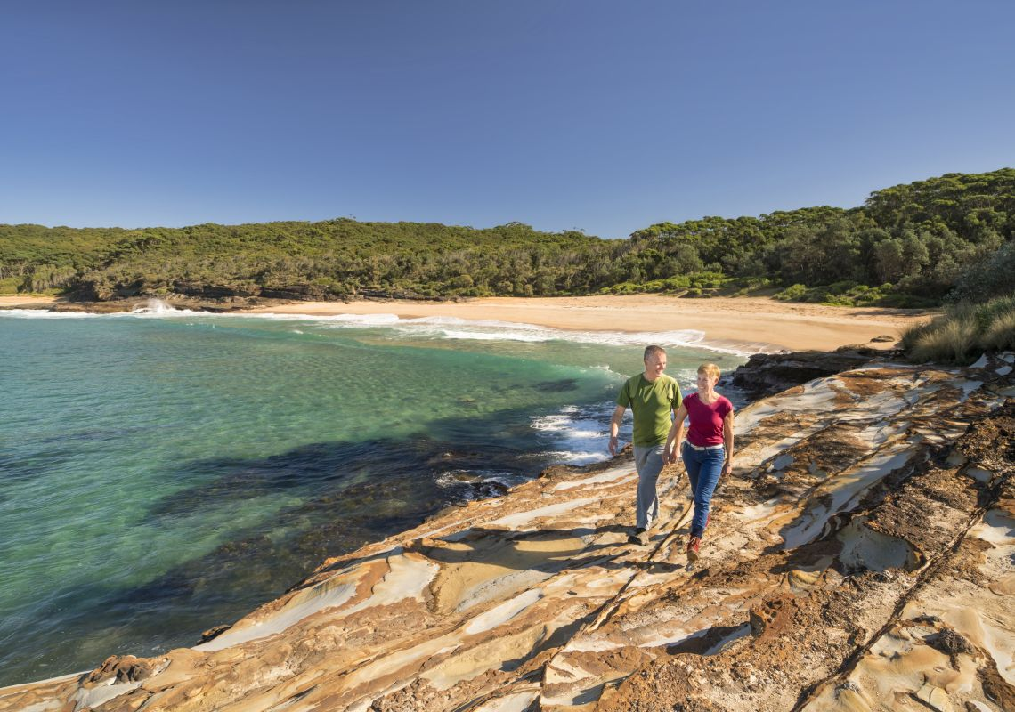 Couple enjoying a scenic morning walk around Wasps Head, Murramarang National Park with views overlooking Wobbegong Bay