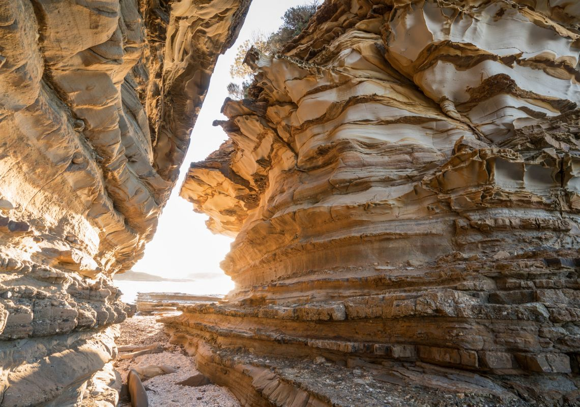 Sun shining through a sandstone passage at Wasps Head in Murramarang National Park