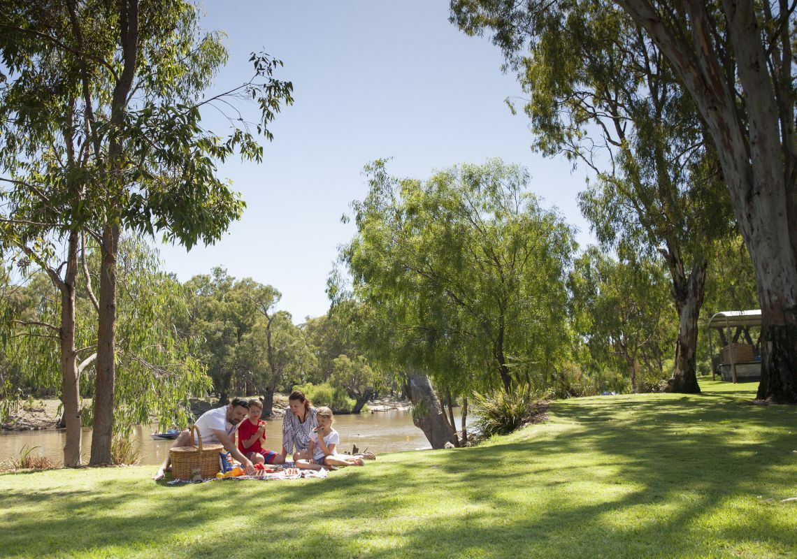 Family enjoying a picnic by the Edward River in Deniliquin, The  Murray, Country NSW