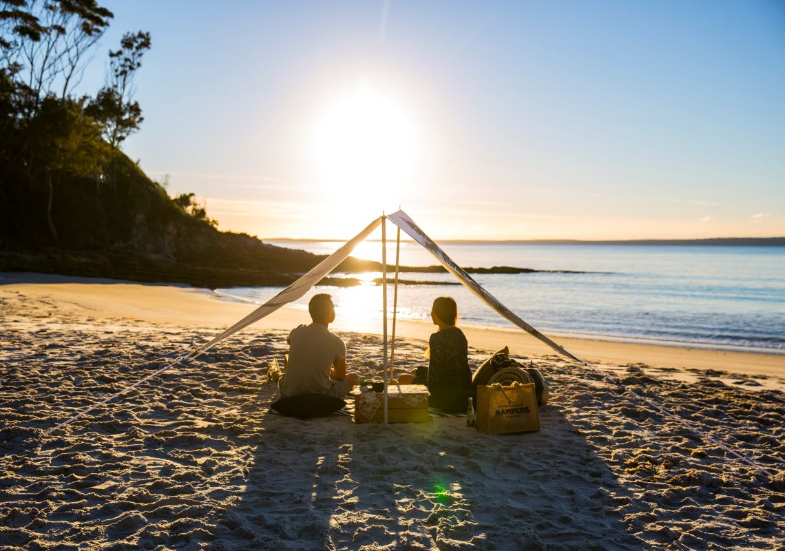 Couple enjoying a picnic packed by Hyams Beach Hampers at Blenheim Beach in Jervis Bay, South Coast