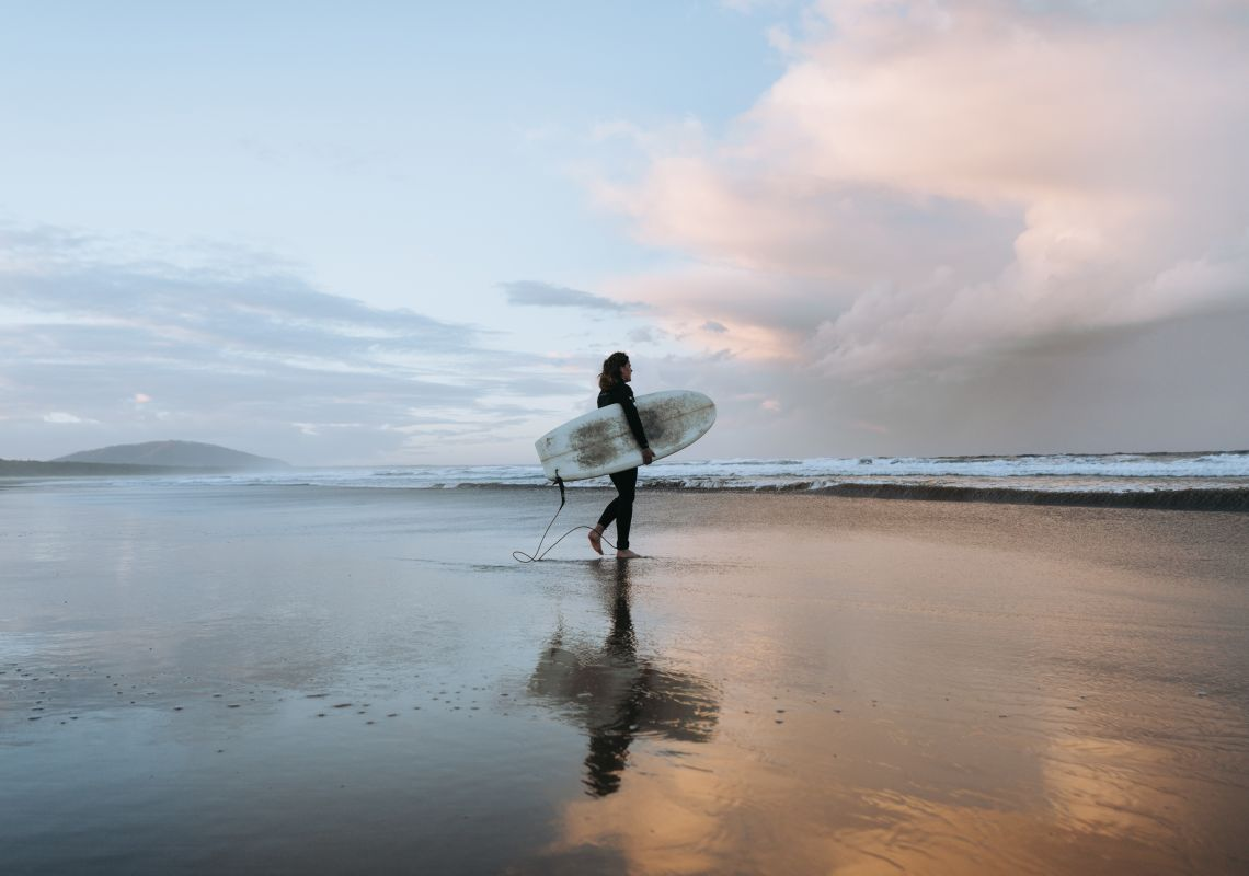 Surfer catching waves at Seven Mile Beach which stretches from Gerroa to Shoalhaven Heads, Kiama Area, South Coast