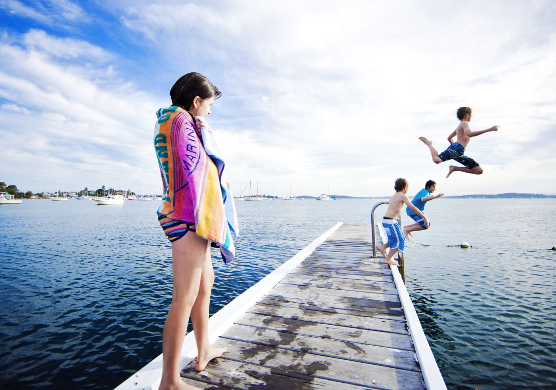 Kids jumping off the Belmont Jetty at Lake Macquarie, North Coast