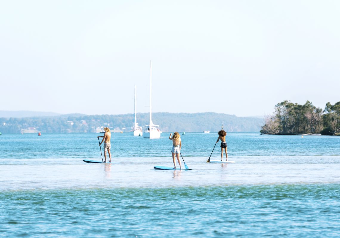 Friends enjoying a day of stand up paddleboarding on Lake Macquarie off Naru Beach