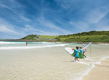 "Children heading out for a surf at Killalea State Park, ""The Farm"""