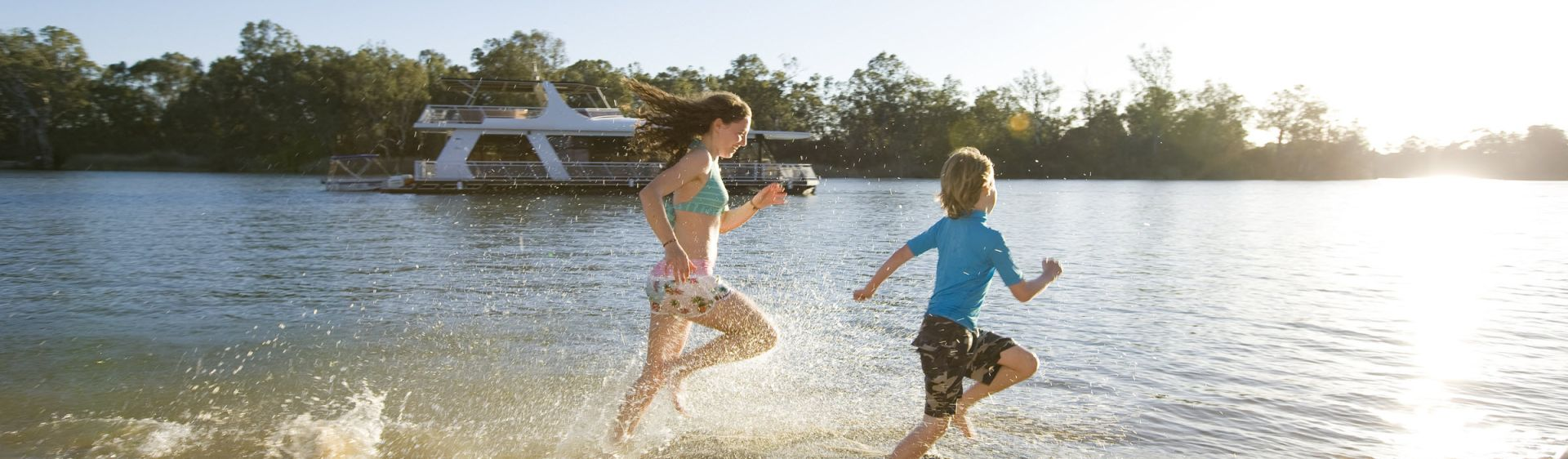 Children running along the bank of the Murray river in The Murray