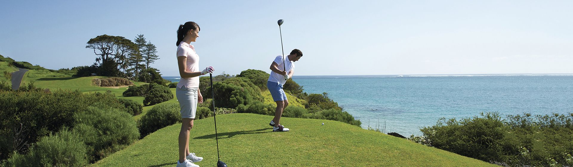 Couple enjoying a round of golf at Lord Howe Island Golf Course, with ocean views
