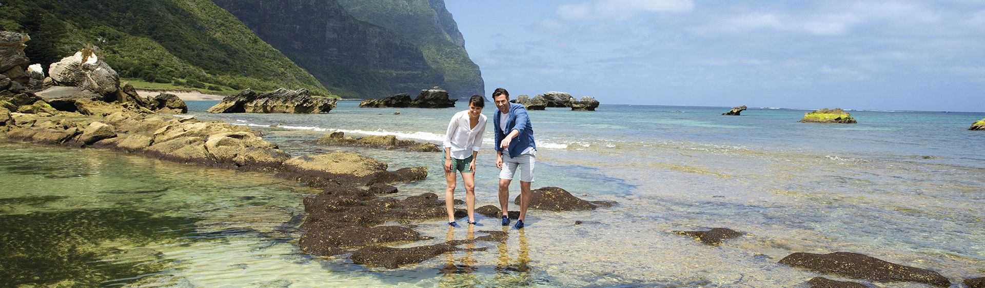 Couple walking along the reef exploring marine life at Johnsons Beach, Lord Howe Island.