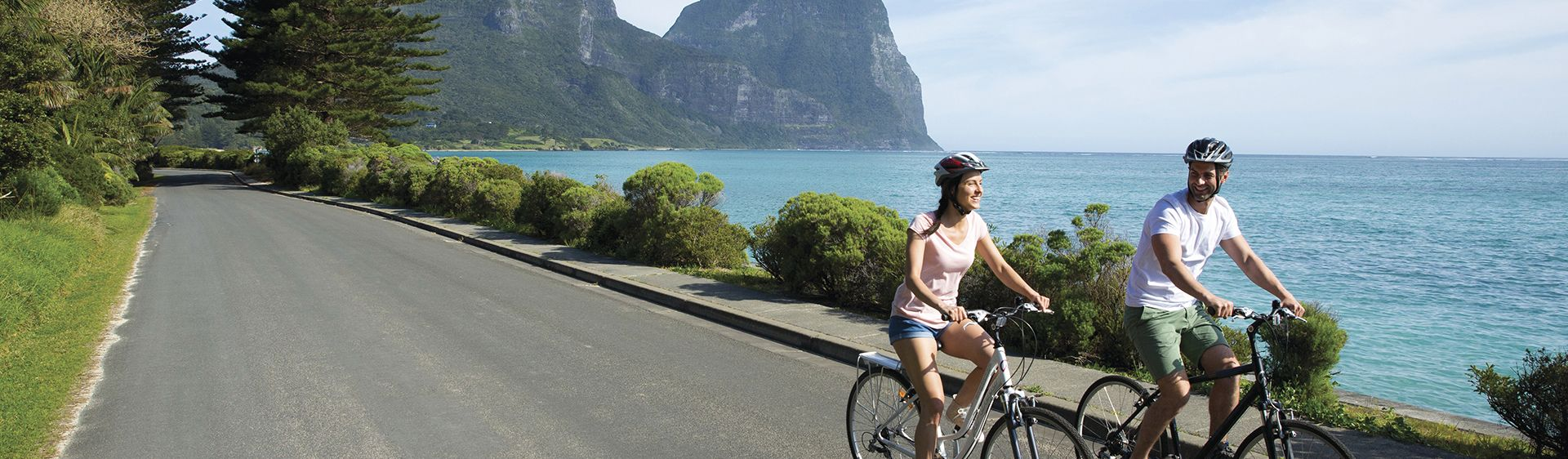 Couple enjoying a relaxing and scenic bike ride on Lord Howe Island.