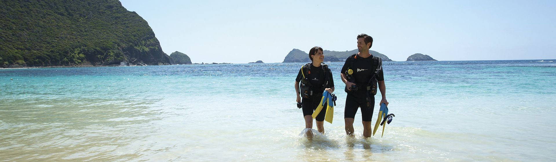 Couple ready to dive from Neds Beach, Lord Howe Island