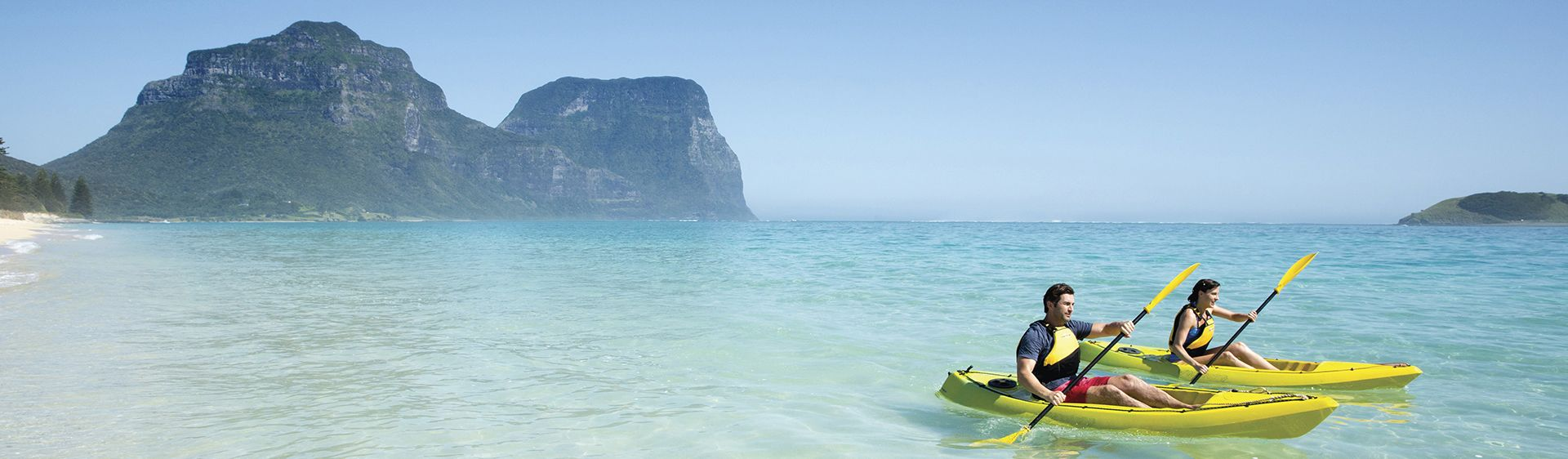 Couple enjoying a scenic kayak by Lagoon Beach on Lord Howe Island with Mount Gower as the backdrop