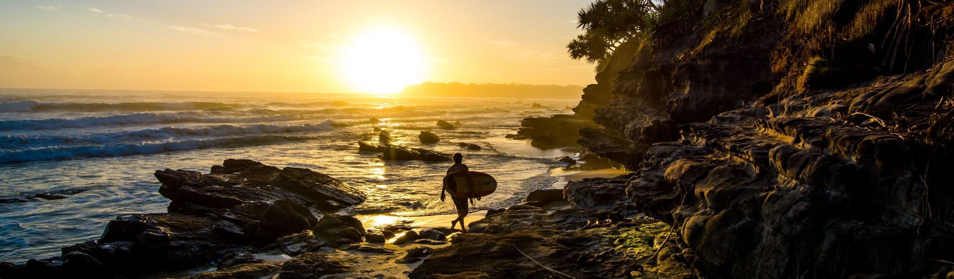 A surfer walks at sunrise on Chinamans Beach, Evans Head