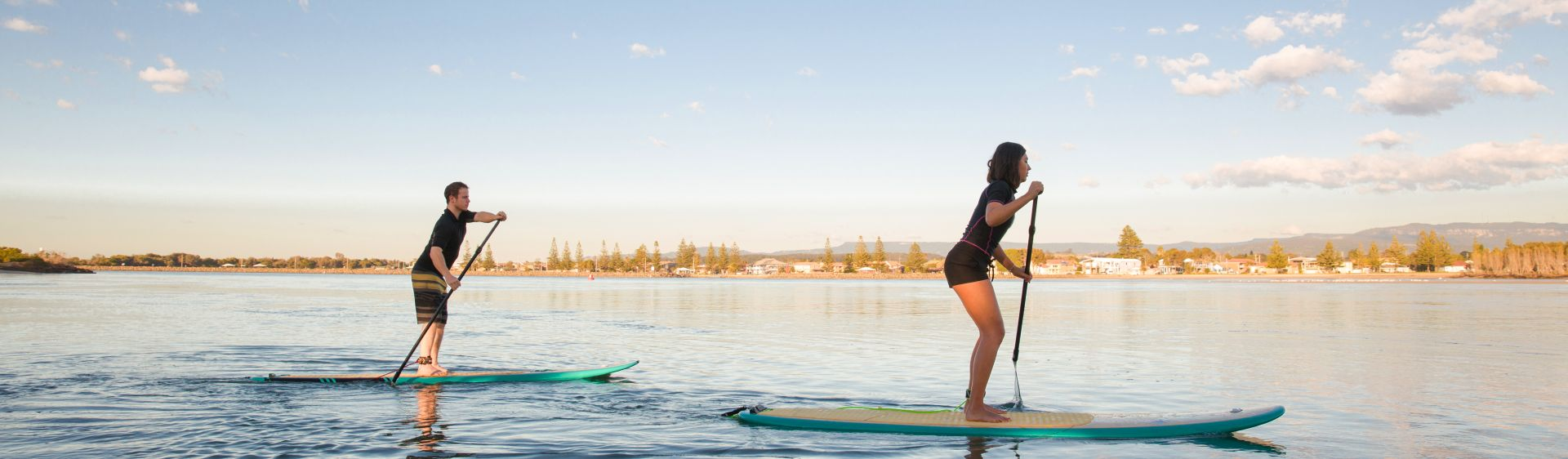 Couple stand-up paddleboarding at Lake Illawarra, Shellharbour, South Coast NSW