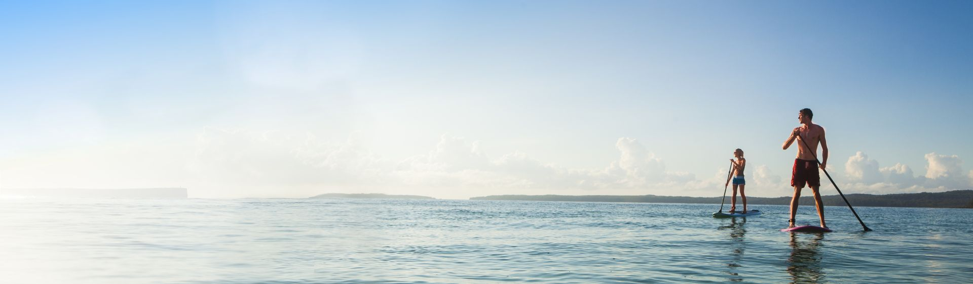 Couple Stand-Up Paddleboarding in Jervis Bay, Shoalhaven, NSW South Coast