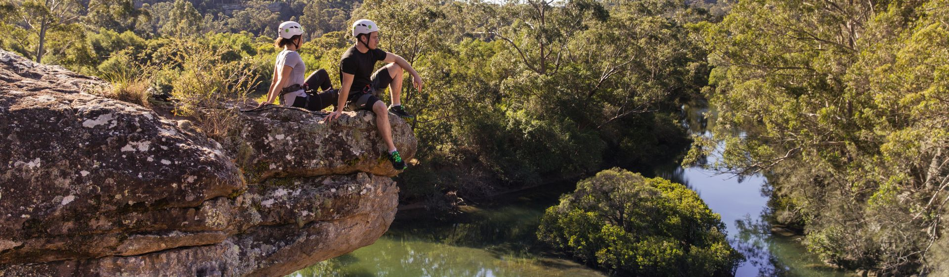 Couple relax on a rock ledge while rock climbing in Nowra, Shoalhaven