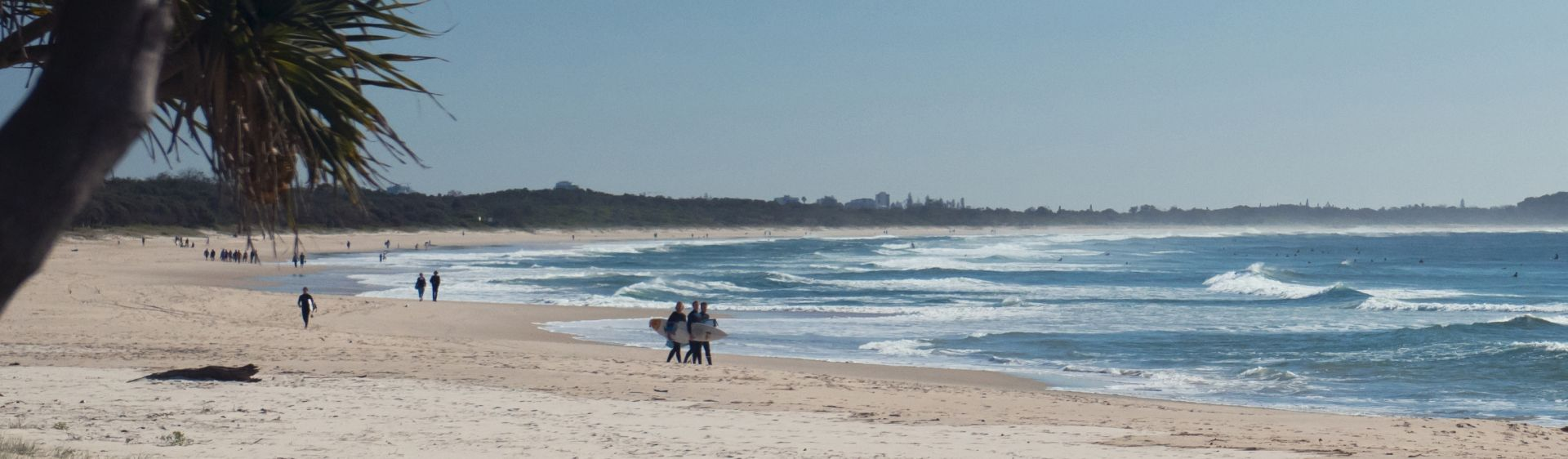 Surfers walking along Kingscliff Beach in The Tweed region.